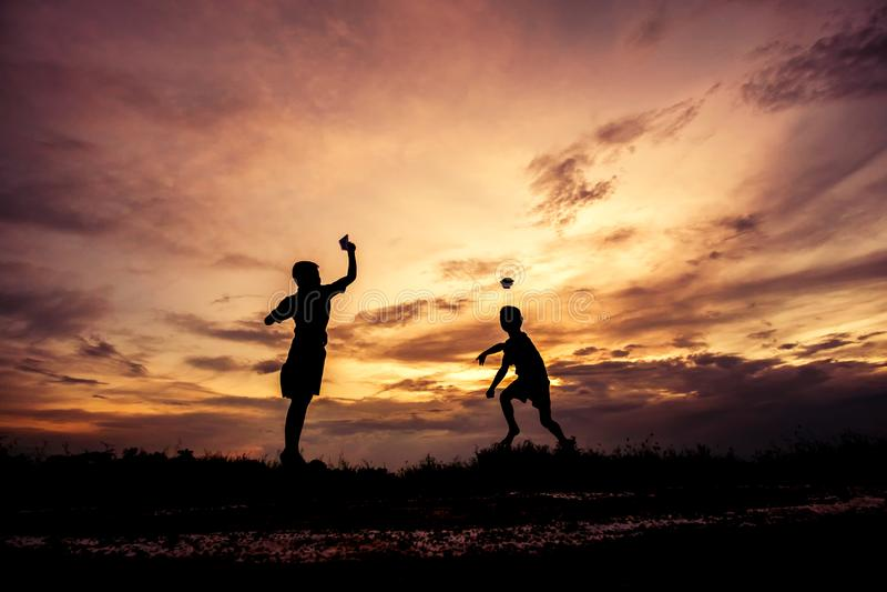 Silhouette des enfants jouant l'avion de papier au coucher du soleil image libre de droits