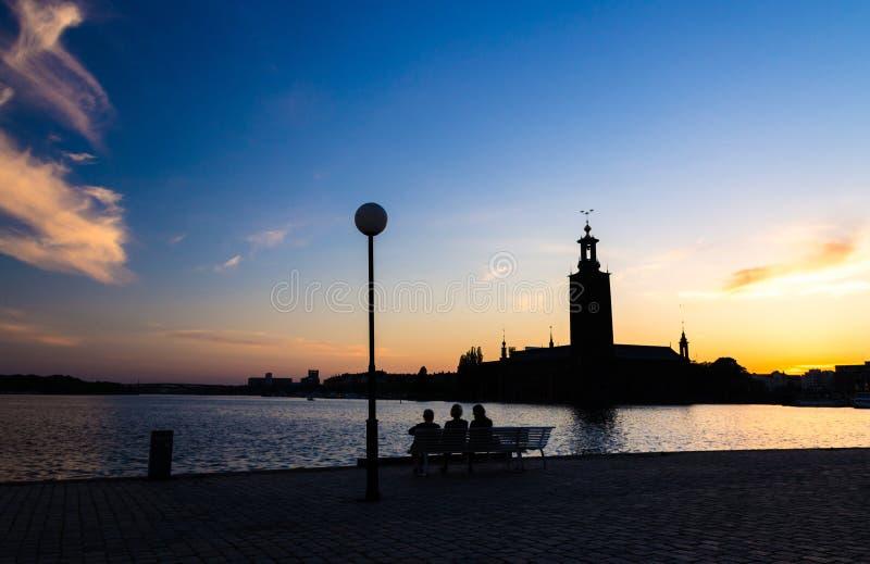 Silhouette des femmes s'asseyant sur le banc, Hôtel de Ville de Stockholm, Suédois image libre de droits