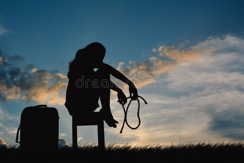 Silhouette des femmes tristes s'asseyant sur la chaise image stock