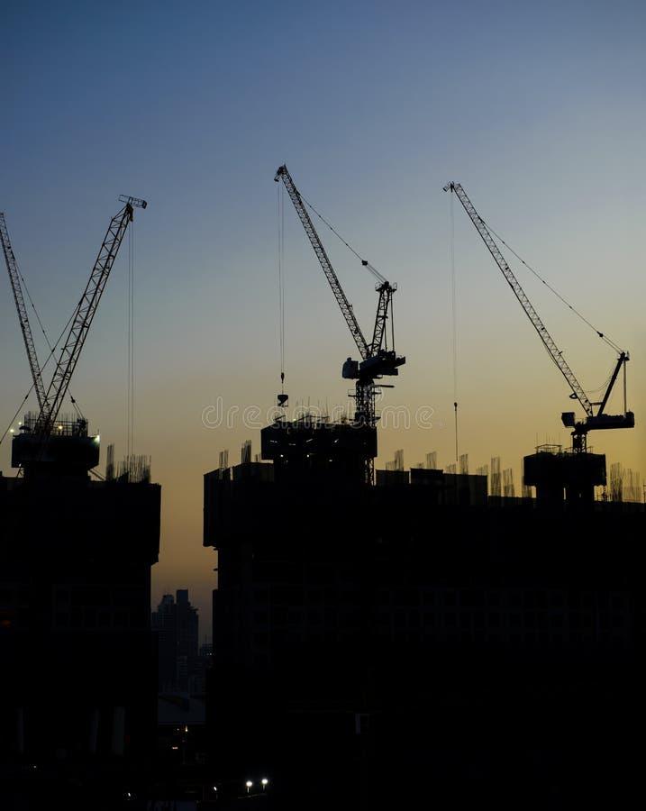 Silhouette des grues à tour au chantier de construction photographie stock