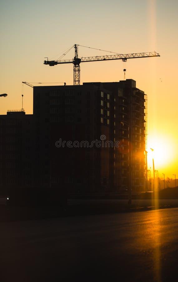Silhouette des grues de construction au-dessus de nouveaux bâtiments résidentiels au coucher du soleil Fond urbain photographie stock
