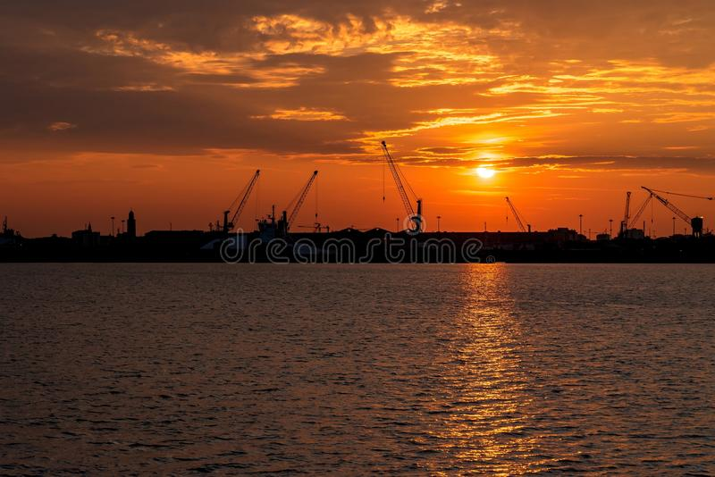 Silhouette des grues de port maritime au lever de soleil Chioggia, Italie photo stock