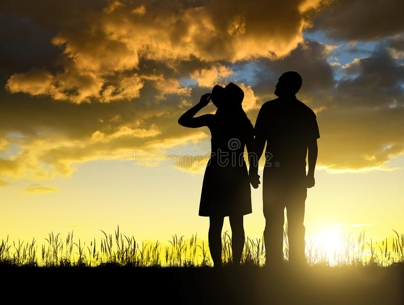 Silhouette des hommes et des femmes tenant des mains photographie stock