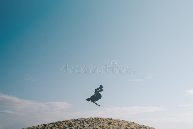 Silhouette des hommes faisant un mouvement acrobatique de culbute à l'envers sur des dunes de sable image libre de droits