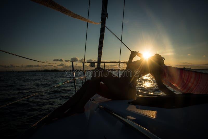 Silhouette des jeunes femmes s'asseyant au bord du voilier images stock