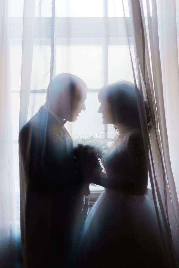 Silhouette des jeunes mariés embrassant tenant le bouquet contre la fenêtre avec des rideaux photographie stock