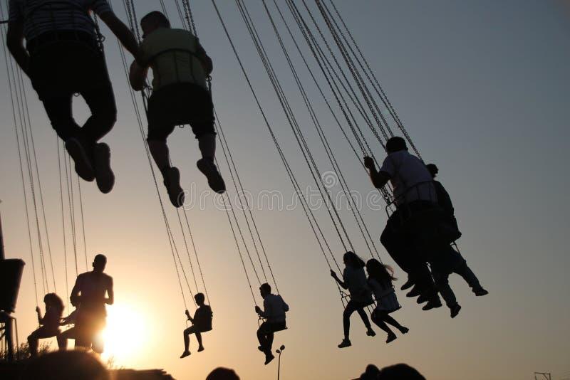 Silhouette des jeunes sur la grande roue et le carrousel de oscillation dans le mouvement d'arrêt sur le fond de coucher du solei photo stock