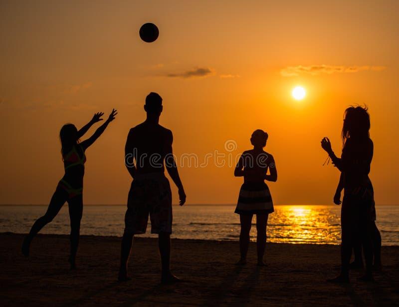 Silhouette des jeunes sur une plage photos stock