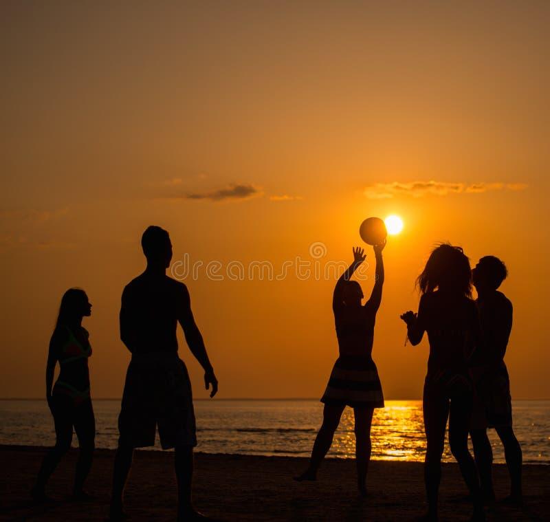 Silhouette des jeunes sur une plage photographie stock