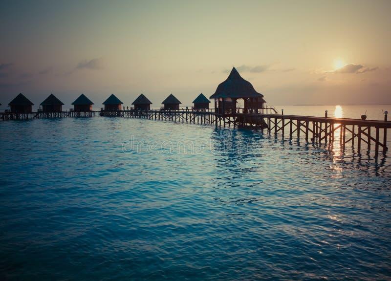 Silhouette des loges en mer au coucher du soleil maldives photo libre de droits