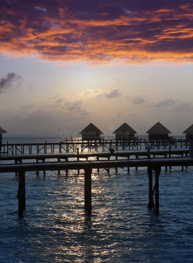 Silhouette des loges en mer au coucher du soleil maldives photos stock