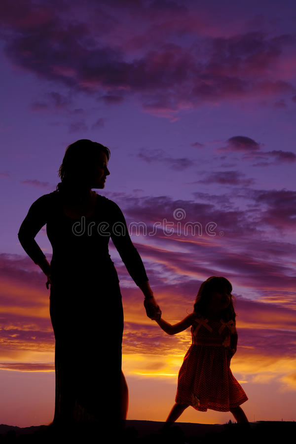 Silhouette des mains de prise de mère et de fille images stock