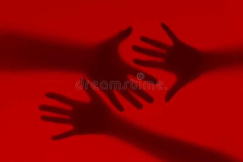 Silhouette des mains masculines et femelles sur un fond rouge photographie stock