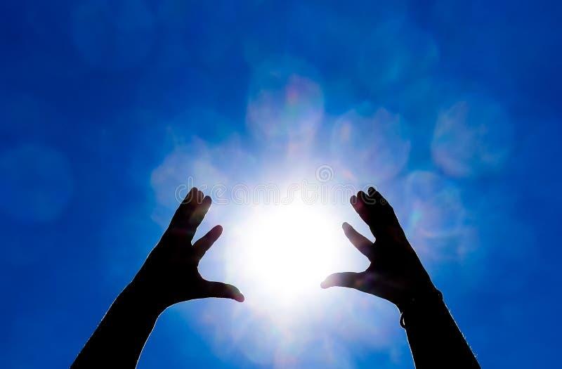 Silhouette des mains sur le fond du soleil et de ciel bleu Des mains sont augmentées jusqu'au images stock