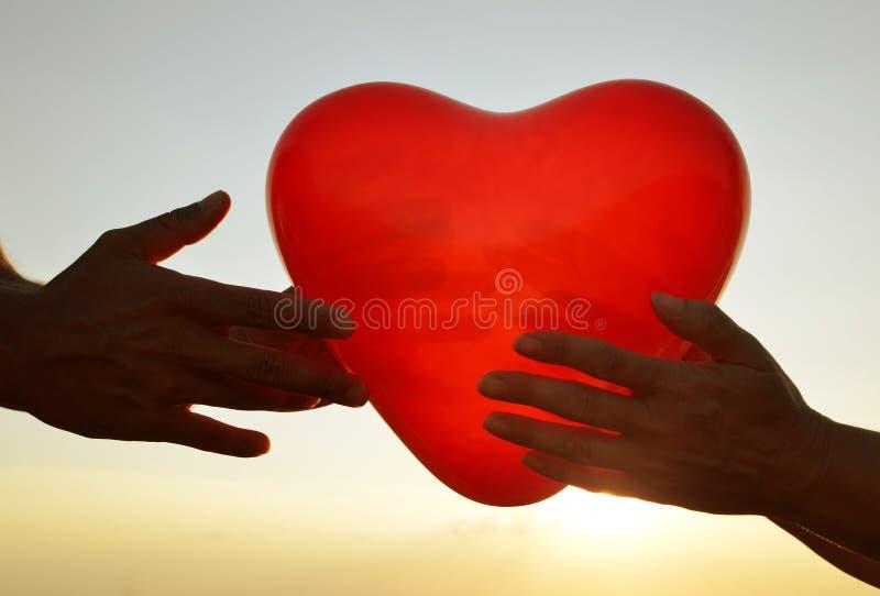 Silhouette des mains tenant le ballon rouge sous forme de coeur photos stock