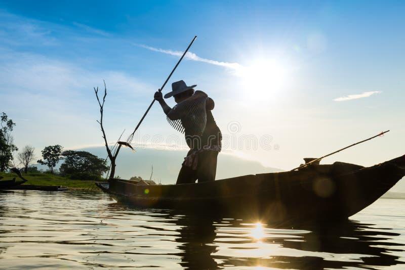 Silhouette des pêcheurs employant les poissons de capture de piège comme une cage en La photo libre de droits