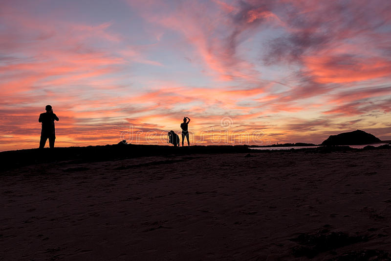 Silhouette des personnes au coucher du soleil sur la plage photographie stock
