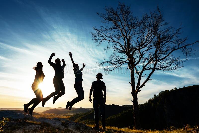 Silhouette des personnes Les gens dans le saut Les amis ont l'amusement au coucher du soleil Amis dr?les Meilleurs amis D?placeme photo libre de droits