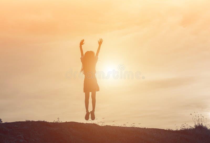 Silhouette des personnes sautant ensemble au coucher du soleil photo libre de droits