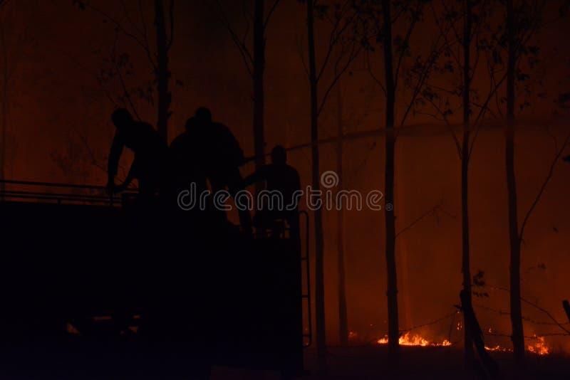 Silhouette des pompiers combattant un feu faisant rage images stock