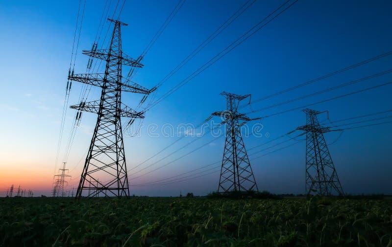Silhouette des pylônes de l'électricité et des lignes électriques à haute tension image stock