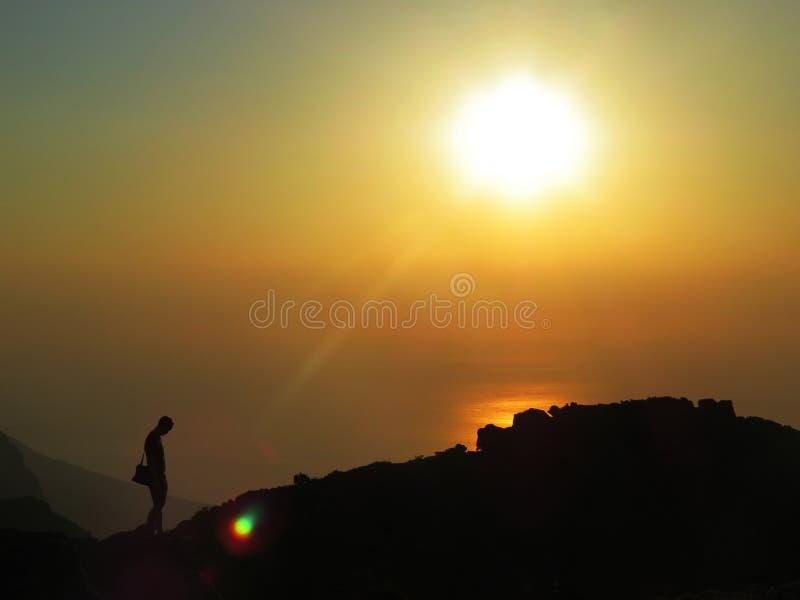 Silhouette devant un coucher du soleil au-dessus de l'océan image libre de droits