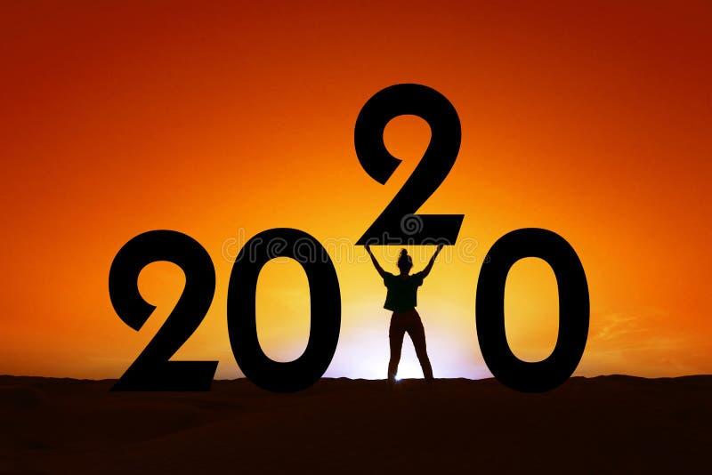 2020 silhouette di una donna in piedi al tramonto, empowerment femminile, cartolina di auguri per il nuovo anno festivo femminile fotografia stock libera da diritti