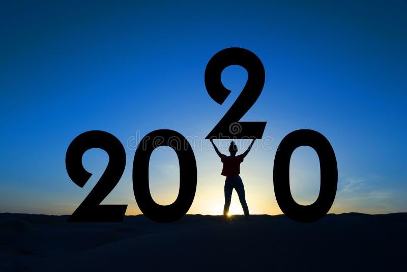 2020, silhouette di una donna in piedi all'alba, empowerment femminile, cartolina festiva per il nuovo anno femminista fotografia stock