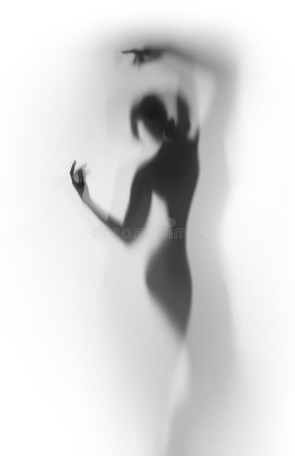 Silhouette diffuse d'une belle femme de danseur derrière un rideau photo libre de droits
