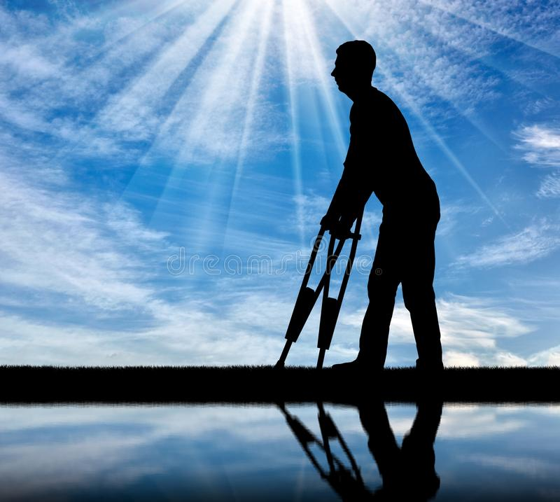 Silhouette of a disabled man with crutches walking near the river with his reflection stock photography