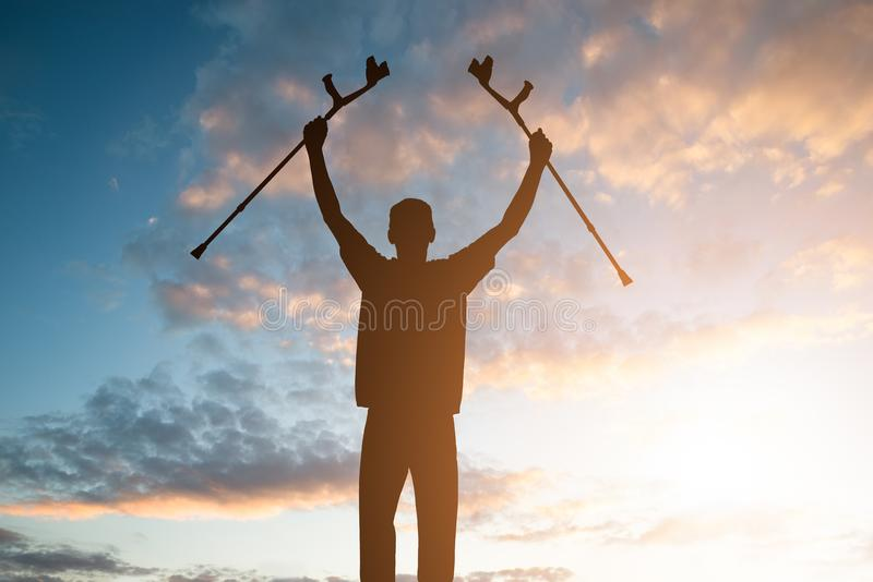 Silhouette Of Disabled Man With Crutches stock photo