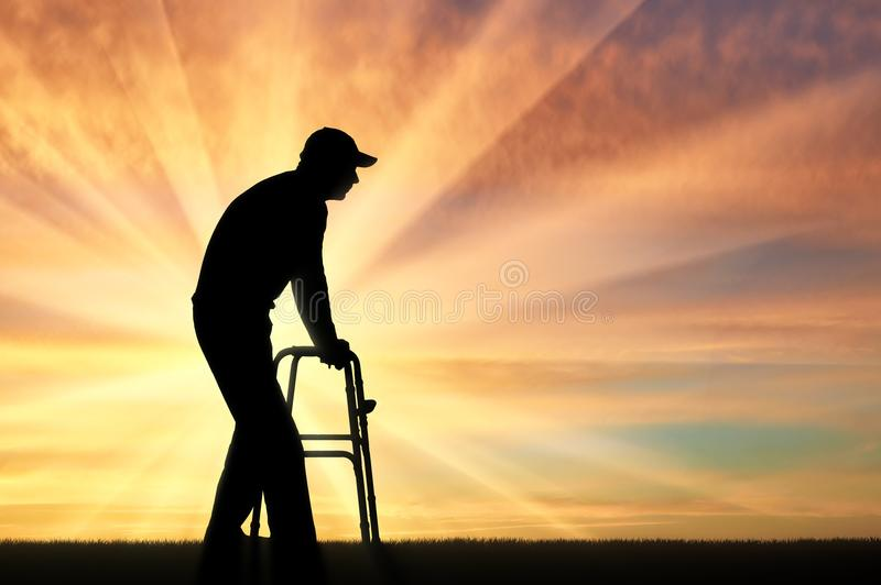 Silhouette of a disabled man walking, using a walker for the disabled stock photos