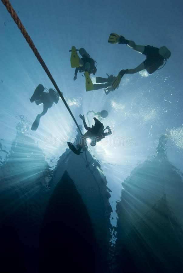 Silhouette of divers and dive boat. royalty free stock photography