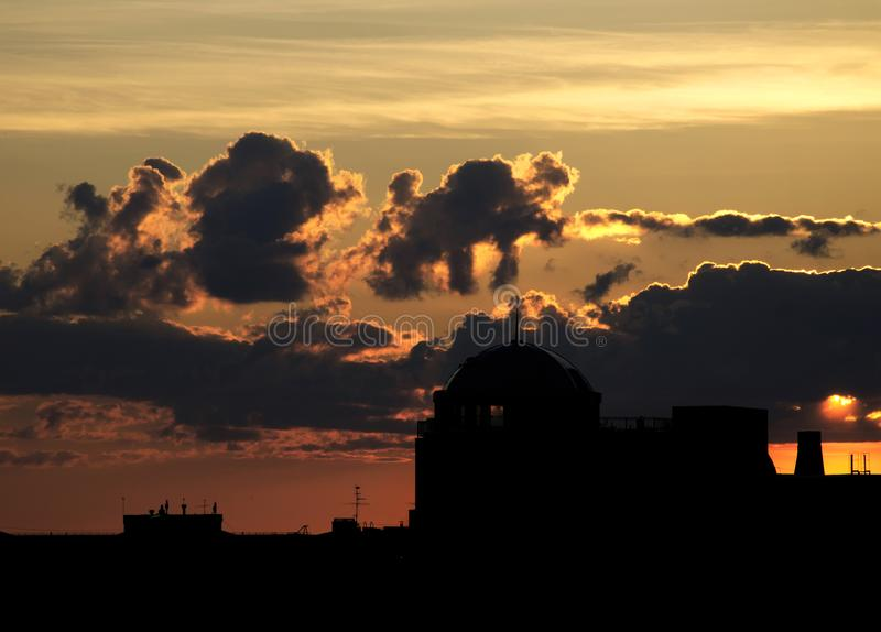 Silhouette of the dome of the building against the sky with different and strange clouds stock photography