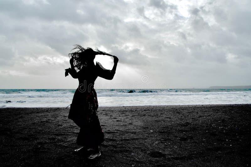 Silhouette dramatique d'une dame aux cheveux longs dans la robe formelle florale sur une plage orageuse photographie stock libre de droits