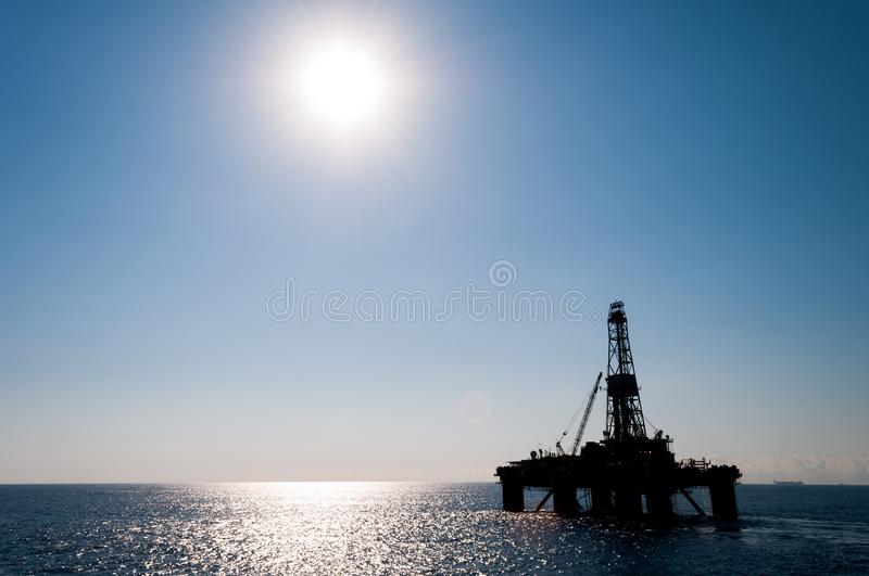 Silhouette of a drilling rig in offshore area. With lots of copy space in the blue sky stock photo