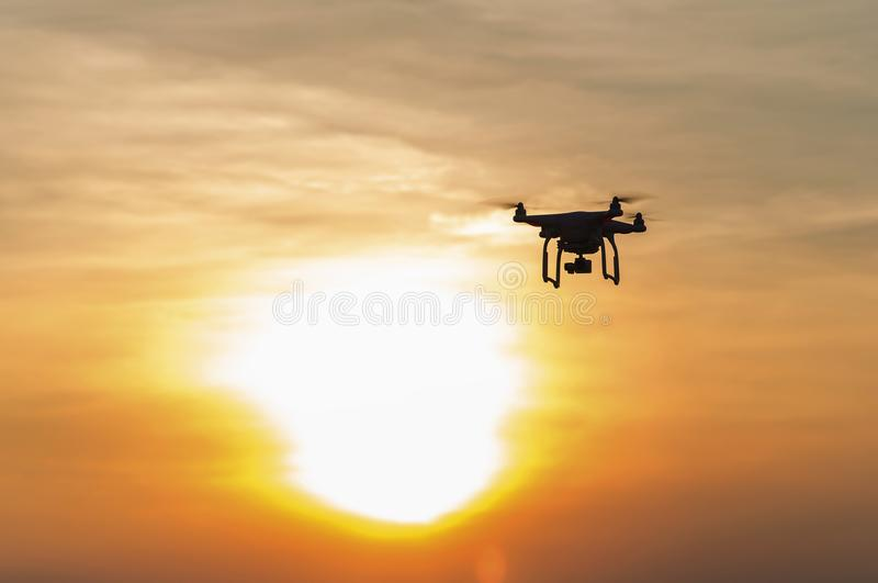Silhouette drone against the background of the sunset. Flying drones in the evening sky. royalty free stock images