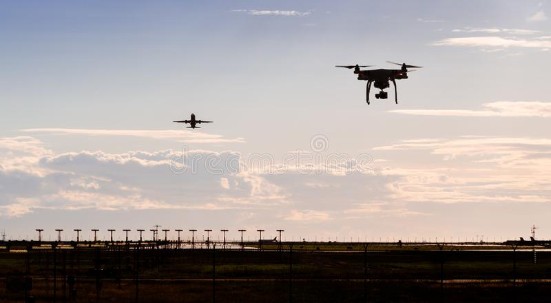 A silhouette of a drone flying near an airport with a aircraft departing in the background. royalty free stock images