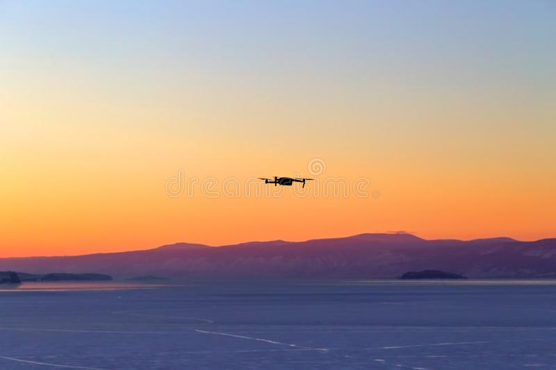 Silhouette of drone flying at sunset on Lake Baikal. Winter time. Photo tour consept stock photos