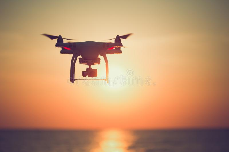 Silhouette of drone hovering in beautiful sunset on the ocean.  royalty free stock image