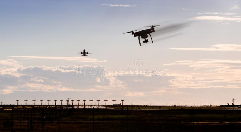 A silhouette of a drone rapidly moving towards an departing aircraft near a airport. royalty free stock photos