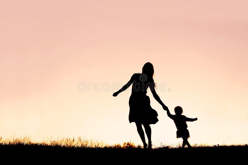 Silhouette du fonctionnement et de la danse de fille de mère et de bébé au Su images libres de droits
