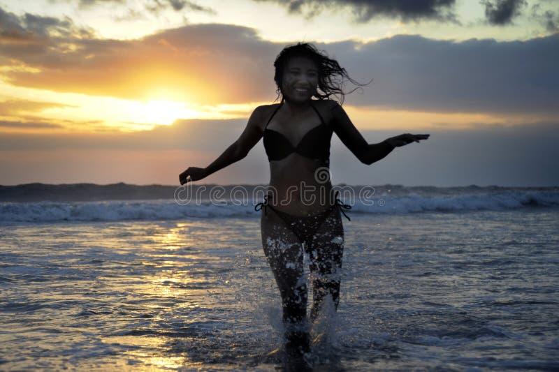 Silhouette du jeune beau et sexy fonctionnement asiatique de femme gratuit et heureux ayant l'amusement à la plage de coucher du  image stock