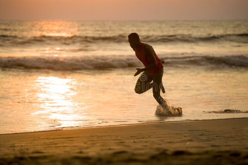 Silhouette du jeune homme américain attirant d'africain noir sportif et fort d'ajustement courant à la formation de plage de couc photo libre de droits