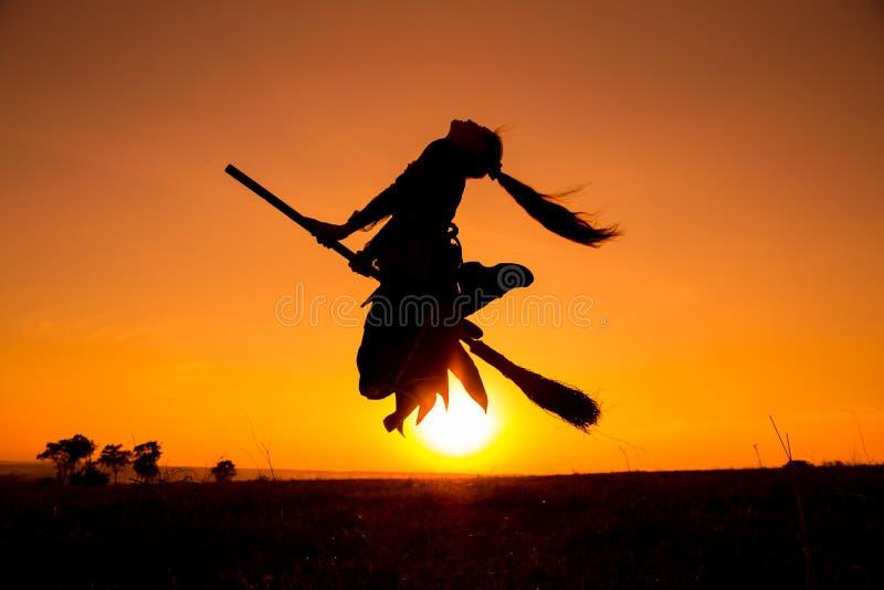 Silhouette du jeune vol de sorcière sur le manche à balai image stock