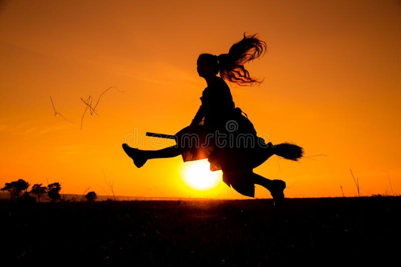 Silhouette du jeune vol de sorcière sur le manche à balai photographie stock libre de droits