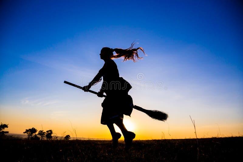 Silhouette du jeune vol de sorcière sur le manche à balai au ciel images stock