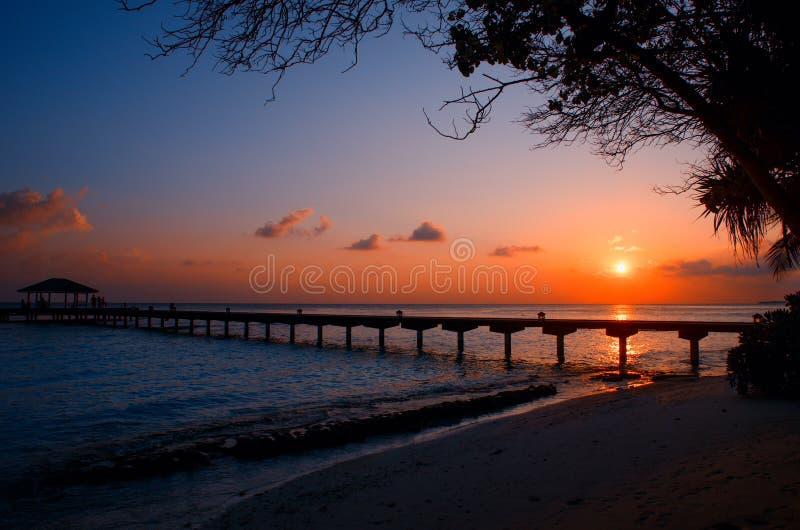 Silhouette du long pilier, pont, pavillon sur le fond d'un coucher du soleil sur des ?les des Maldives Horizontal de nuit images libres de droits