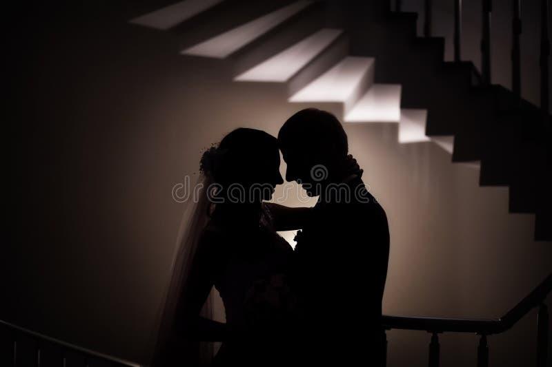 Silhouette du mariage l'amour de jeunes mariés images stock