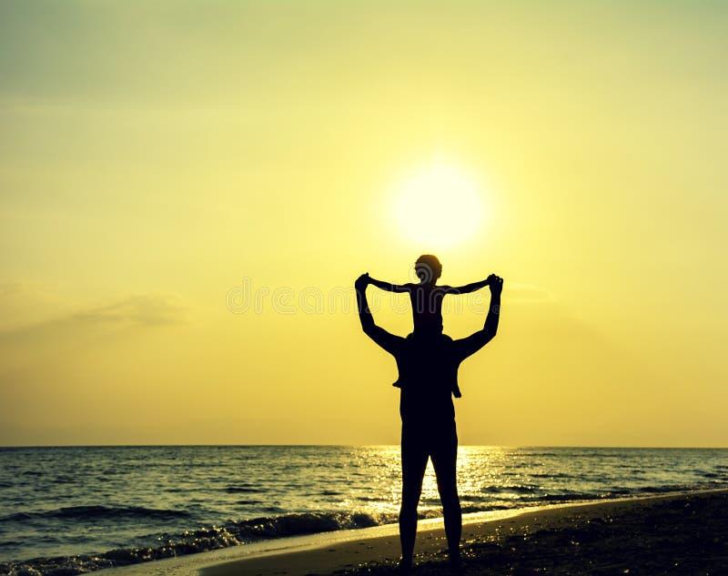 Silhouette du père et du fils appréciant le coucher du soleil et la vie images stock